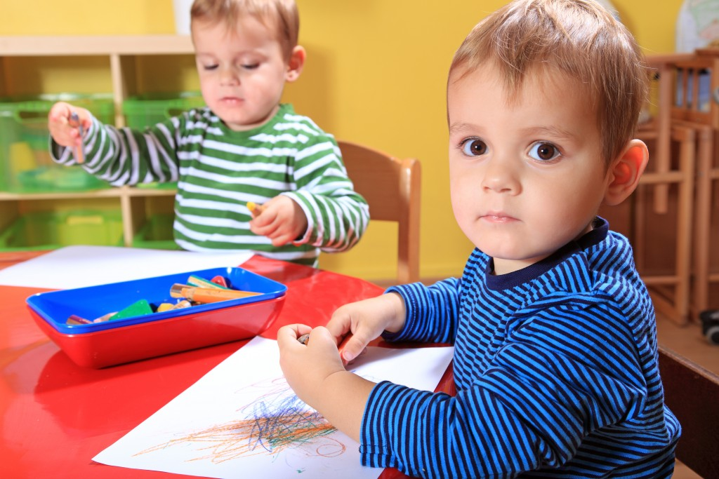 Two little boys coloring on paper