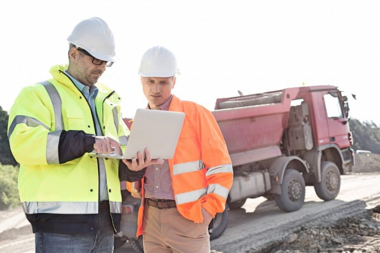 construction workers looking at a laptop